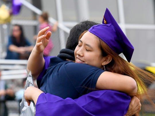 Diploma in hand, graduate Eunice Jin Kim receives a