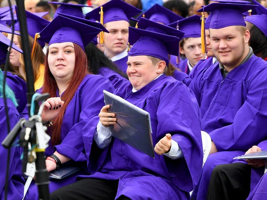 A graduate celebrates with diploma in hand after sitting