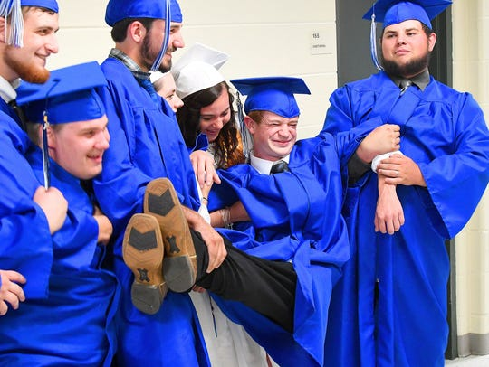 Graduate Michael Martin is held by classmates as they
