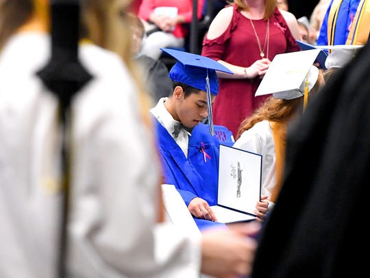 A graduate looks at his diploma after returning to
