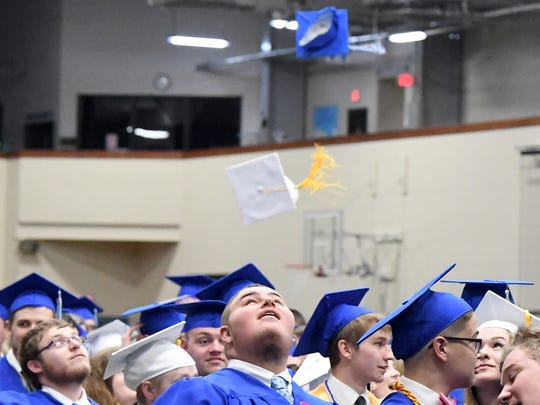 A graduate looks up as they toss their caps into the