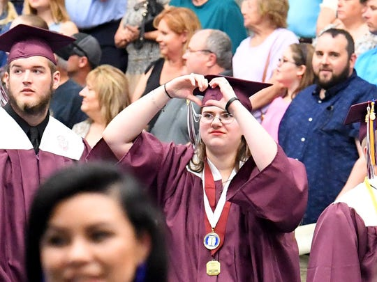 A graduate makes a heart with her hands as she communicates