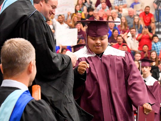 Graduate Samuel Guzman fist bumps a member of the faculty