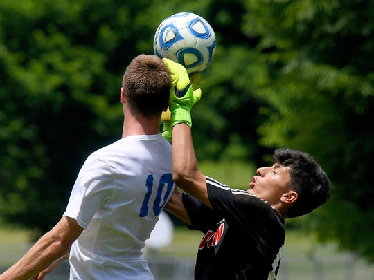 George Mason goalie Zain Hemeed (right) tries to stop the ball after it is headed by Robert E. Lee's Kyle Stenzel to score Lee's first goal of the game. R.E. Lee defeated George Mason, 3-0, to win the Region 2B boys soccer championship during a game played in Staunton on Friday, June 1, 2018.
