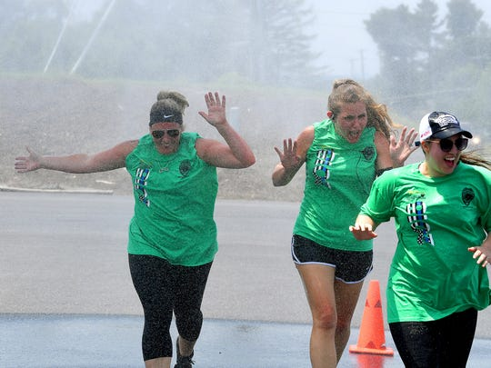 Escorting the Special Olympics torch, the Augusta County SheriffÕs Office and other law enforcement agencies leave U.S. 250 long enough to run through a mist cooling station, set up by Augusta County Fire Department, in Fishersville  during the Law Enforcement Torch Run for Special Olympics on Thursday, June 7, 2018. They participate in the 1,900-mile, 8-day Torch Run which involves more than 2,000 law enforcement officers and personnel with 300 law enforcement agencies across Virginia.