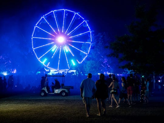 Concertgoers walk past the ferris wheel during the