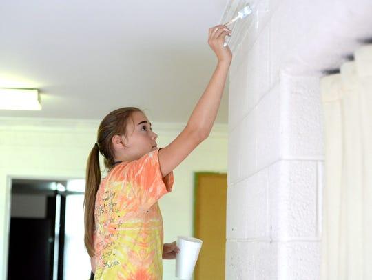 Kayleigh Hostetter, 14, helps paint at Wayne Hills