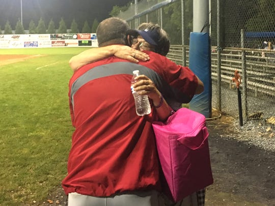 George Laase gets a hug from a fan following Monday's game at Staunton's Moxie Stadium. Laase, who coached Staunton for five years, is now a member of the Harrisonburg Turks' coaching staff.