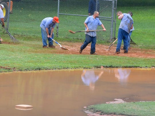 Second base is surrounded by water as inmates with Middle River Regional Jail work to cleanup one of the ballfields, following the previous day's flooding, at Gypsy Hill Park on Friday, June 22, 2018.