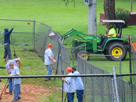 Inmates with Middle River Regional Jail work to cleanup one of the ballfields following the previous day's flooding as a Staunton Parks and Recreation worker uses a tractor to push a chainlink fence back up and into place at Gypsy Hill Park on Friday, June 22, 2018.