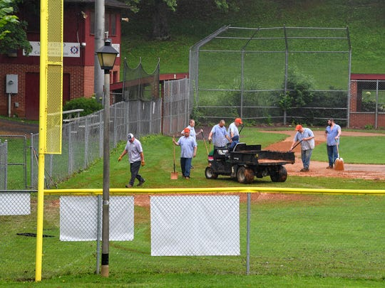 Inmates with Middle River Regional Jail work to cleanup one of the ballfields, following the previous day's flooding, at Gypsy Hill Park on Friday, June 22, 2018.