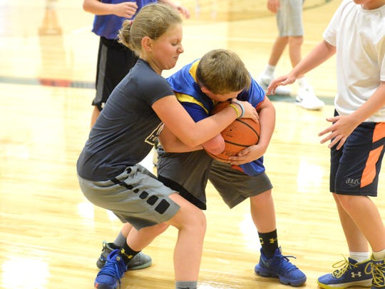 Logan Hoover, left, battles Beckett Ryder for the ball during the Wilson Memorial basketball camp Monday in Fishersville.