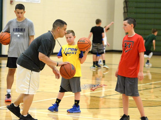 Beckett Ryder (center) watches Wilson Memorial boys basketball coach Jeremy Hartman during a camp in Fishersville Monday.