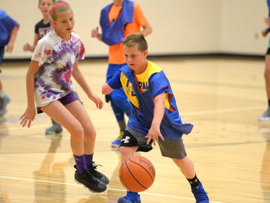 Beckett Ryder, 9, who was born missing part of his right arm, dribbles during a game at the Wilson Memorial basketball camp Monday.