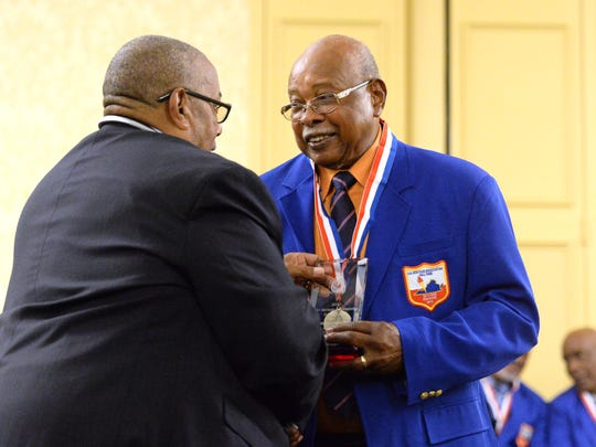 Former Booker T. Washington basketball coach Al Hamilton, right, is congratulated by Jimmy Hollins, chairman of the VIA Heritage Association, Friday night during the organization's hall of fame ceremony in Charlottesville.