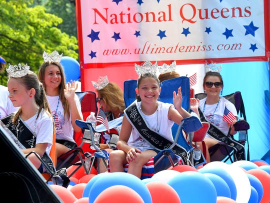 America's Ultimate Miss National Queens wave to the crowd as they share a float in the Happy Birthday America Parade at Gypsy Hill Park in Staunton on Wednesday, July 4, 2018.
