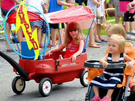 One young parade participated rides the parade route under the canopy of her wagon. The Happy Birthday America Parade made its way through Gypsy Hill Park in Staunton on Wednesday, July 4, 2018.