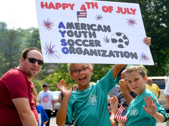 Parade goers aboard the American Youth Soccer Organization's float wave to the crowd while one holds high a sign wishing everyone a happy 4th of July. The Happy Birthday America Parade made its way through Gypsy Hill Park in Staunton on Wednesday, July 4, 2018.