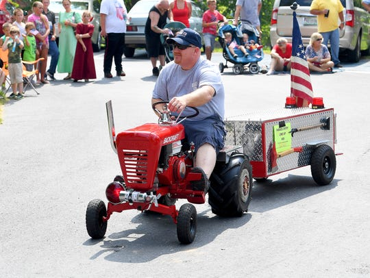 One man rings the bell of his small tractor as he travels