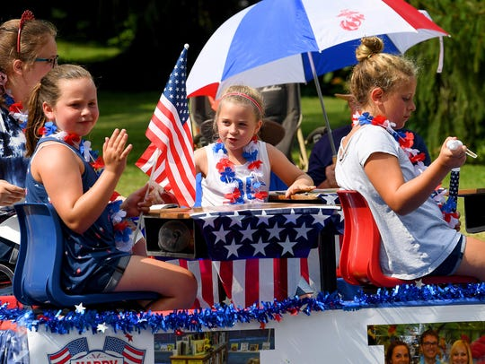 Young parade goers share a float as they travel the