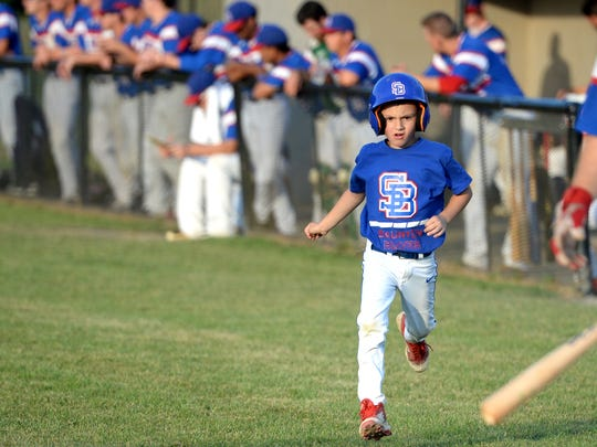 Ethan Carper, 7, runs onto the field at Kate Collins