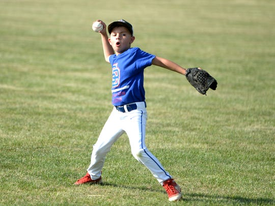 Ethan Carper, 7, has a game of catch on Saturday, June
