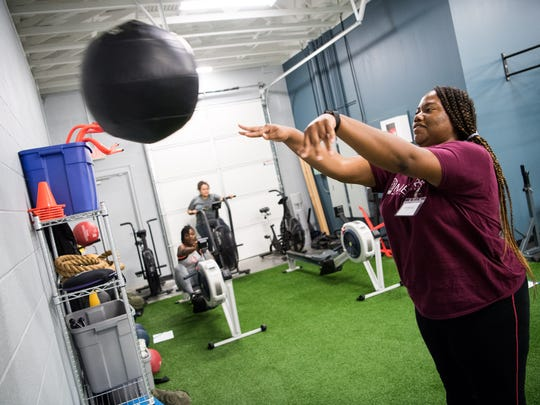 Kimberly Zirker tosses a weighted ball during a fitness