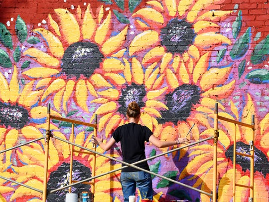 The sunflowers she paints tower above Madeline Maas, a homeschool graduate from Waynesboro, as she paints a mural on a building on Greenville Avenue in downtown Staunton near the giant watering can on Friday, July 27, 2018.
