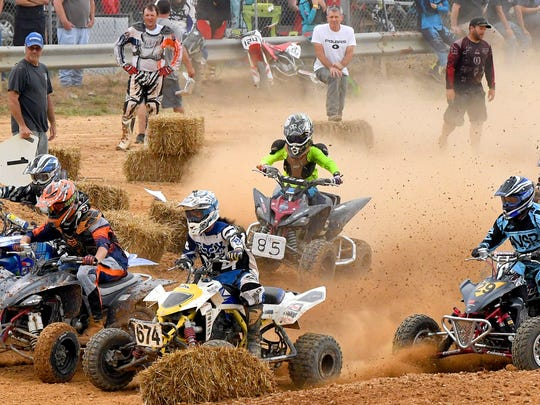 Riders on ATVs come together as they compete in motocross