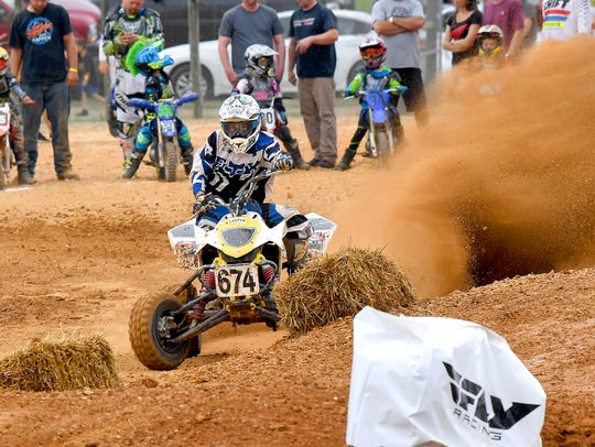 A rider kicks up dirt and dust with his ATV as he rounds