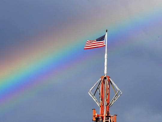 A rainbow paints the sky behind an American flag that