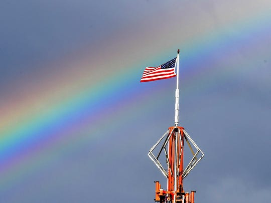 A rainbow paints the sky behind an American flag that flies over the midway at the Augusta County Fair on Wednesday, August 1, 2018.