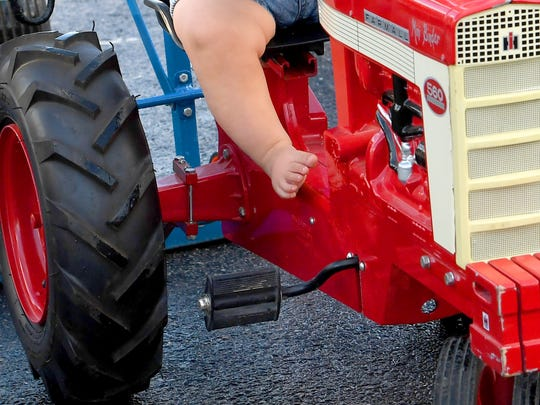 Eight-month-old Henry Wimer receives a little help as his feet don't quite reach the pedals yet. He competes in the kids pedal tractor pull competition at the Augusta County Fair on Wednesday, August 1, 2018.