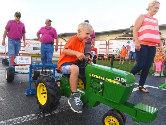 Karper Miller, 4, digs deep to keep the John Deere tractor moving forward, competing in the kids pedal tractor pull competition at the Augusta County Fair on Wednesday, August 1, 2018.