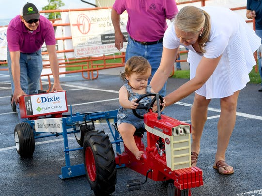 Eight-month-old Henry Wimer receives a little help as he sits astride the Farmall tractor, competing in the kids pedal tractor pull competition at the Augusta County Fair on Wednesday, August 1, 2018.