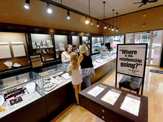 Becky Corns, co-owner of Crown Jewelers, assists customers