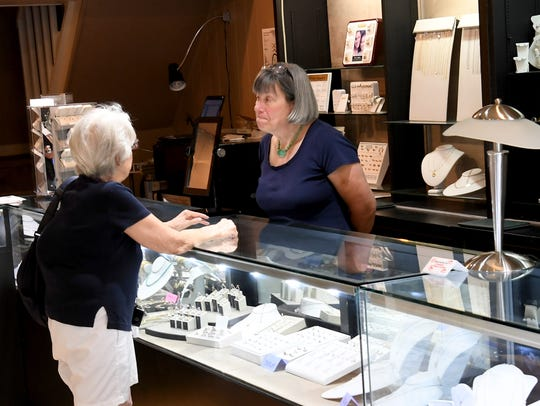 Dana Flanders, co-owner of Crown Jewelers, assists