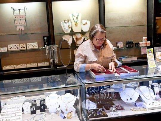 Becky Corns, co-owner of Crown Jewelers, looks for