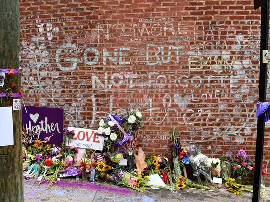 Messages written in chalk fill a brick wall where Heather