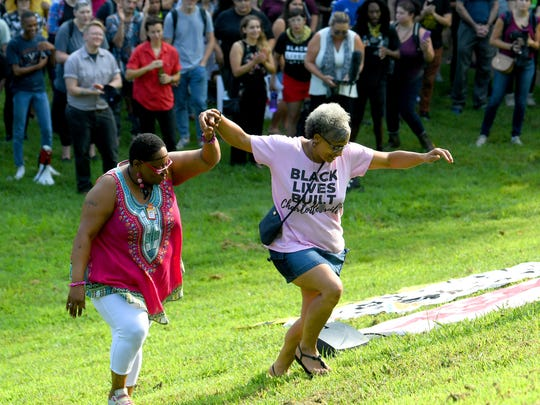 Rosa Parker and Katrina Turner make their way up the hill to speak to the crowd at a rally held at Booker T. Washington Park in Charlottesville, Va., on Sunday, August 12, 2018. The day marked the anniversary of the deadly protests last year.