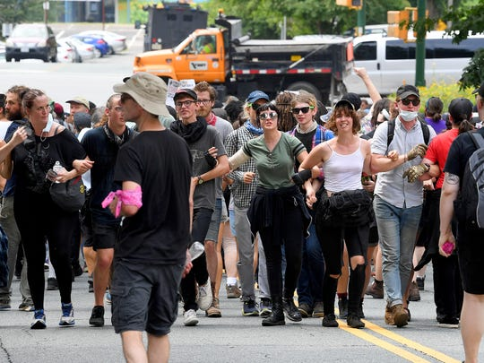 Protesters maintain a line, slowly backing away from approaching law enforcement in Charlottesville, Va., on Sunday, August 12, 2018. The day marked the anniversary of the deadly protests last year.