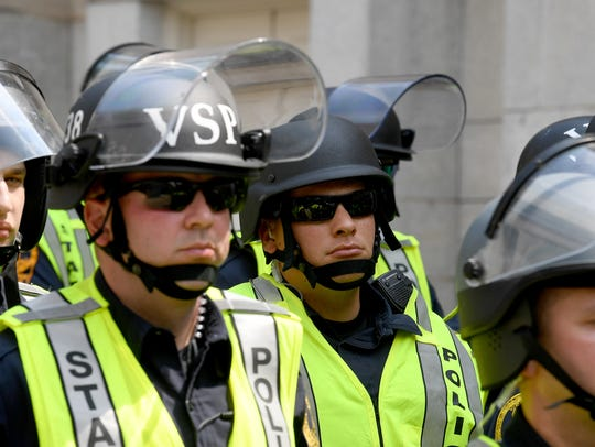 State Police officers with riot helmets are held in