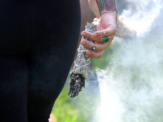 A few people walked among the crowd burning sage at