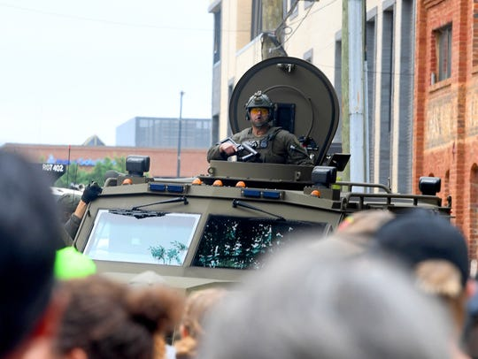 An armored vehicle rolls up and holds position on one