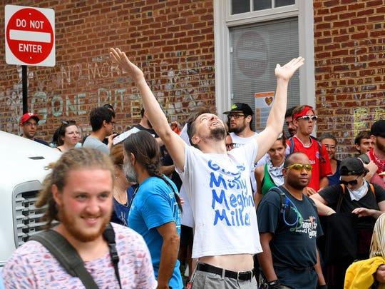 Adam Rhea of Charlottesville raises his hands in celebration