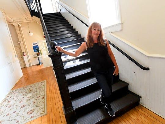 Julie Devine, the building's new owner, stands inside