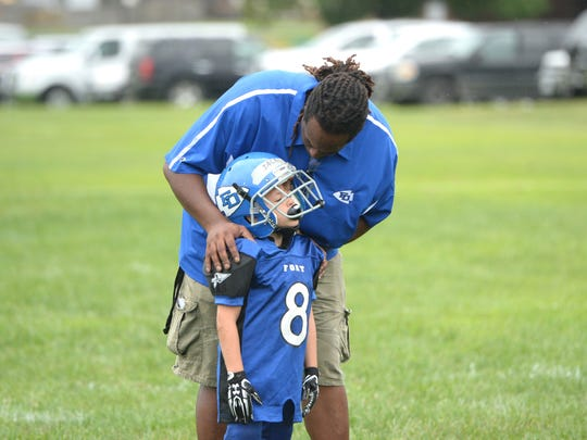 Fort Defiance midget football coach Alphonzo Bruce talks to one of his players before the start of a scrimmage Saturday at the Augusta County Quarterback Club Jamboree in Fishersville.