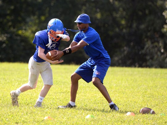 Grace Christian assistant football coach Ernest Morgan hands off to A.J. Holmes during practice Wednesday, Aug. 22.
