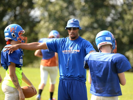 Grace Christian assistant coach Ernest Morgan works with Kshawn McCarthy, left, and A.J. Holmes during football practice Wednesday, Aug. 22.