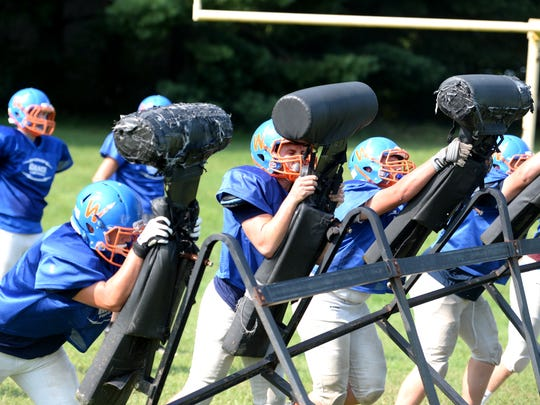 Grace Christian linemen Derrick Weeks (from left), Tommy Hottinger, Jacob Simmons and Ryan Damron work with the blocking sled during practice Wednesday, Aug. 22.
